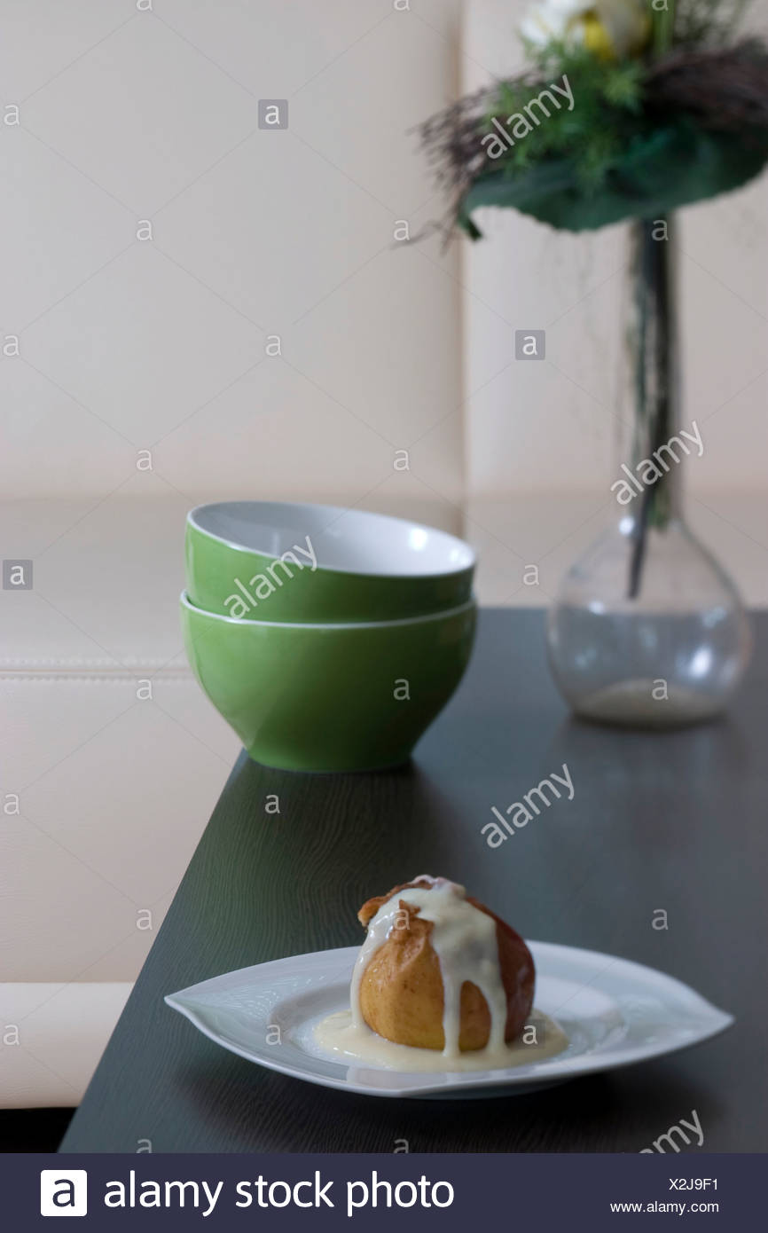 Baked apple filled with marzipan, dusted with cinnamon and covered in vanilla sauce on a plate, served in living room - Stock Image