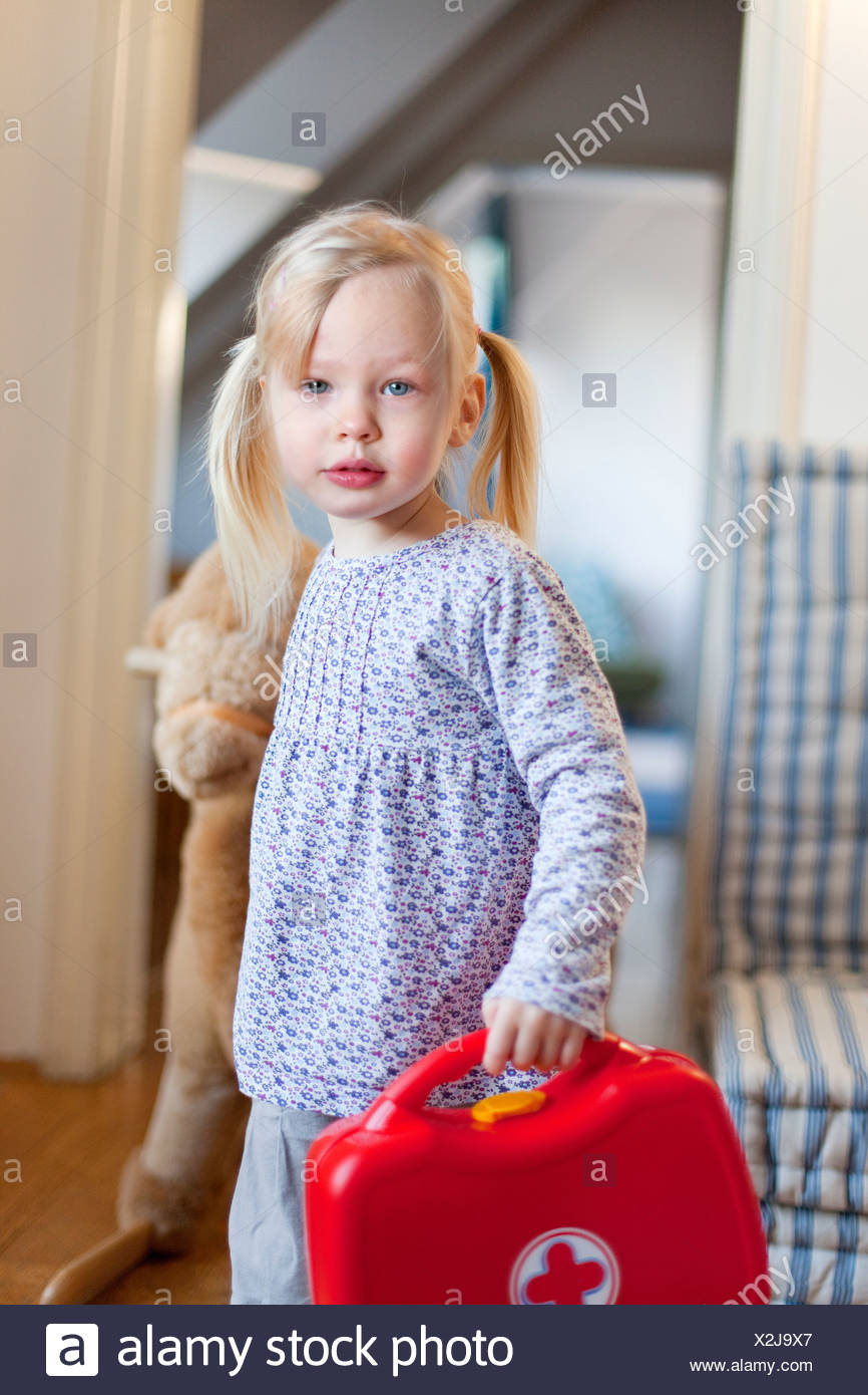 Girl carrying toy first aid kit Stock Photo