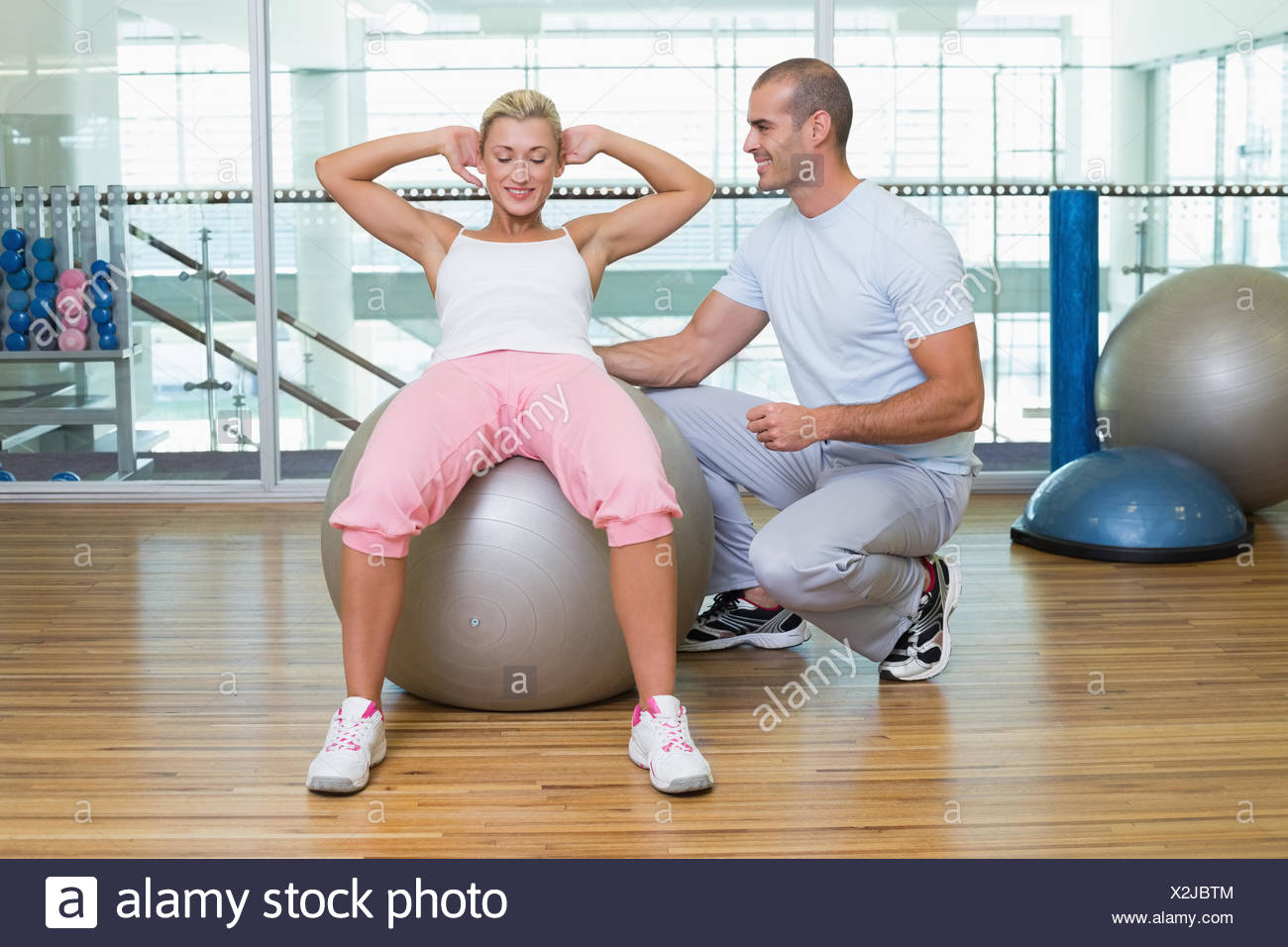 Male trainer assisting woman with abdominal crunches at gym - Stock Image