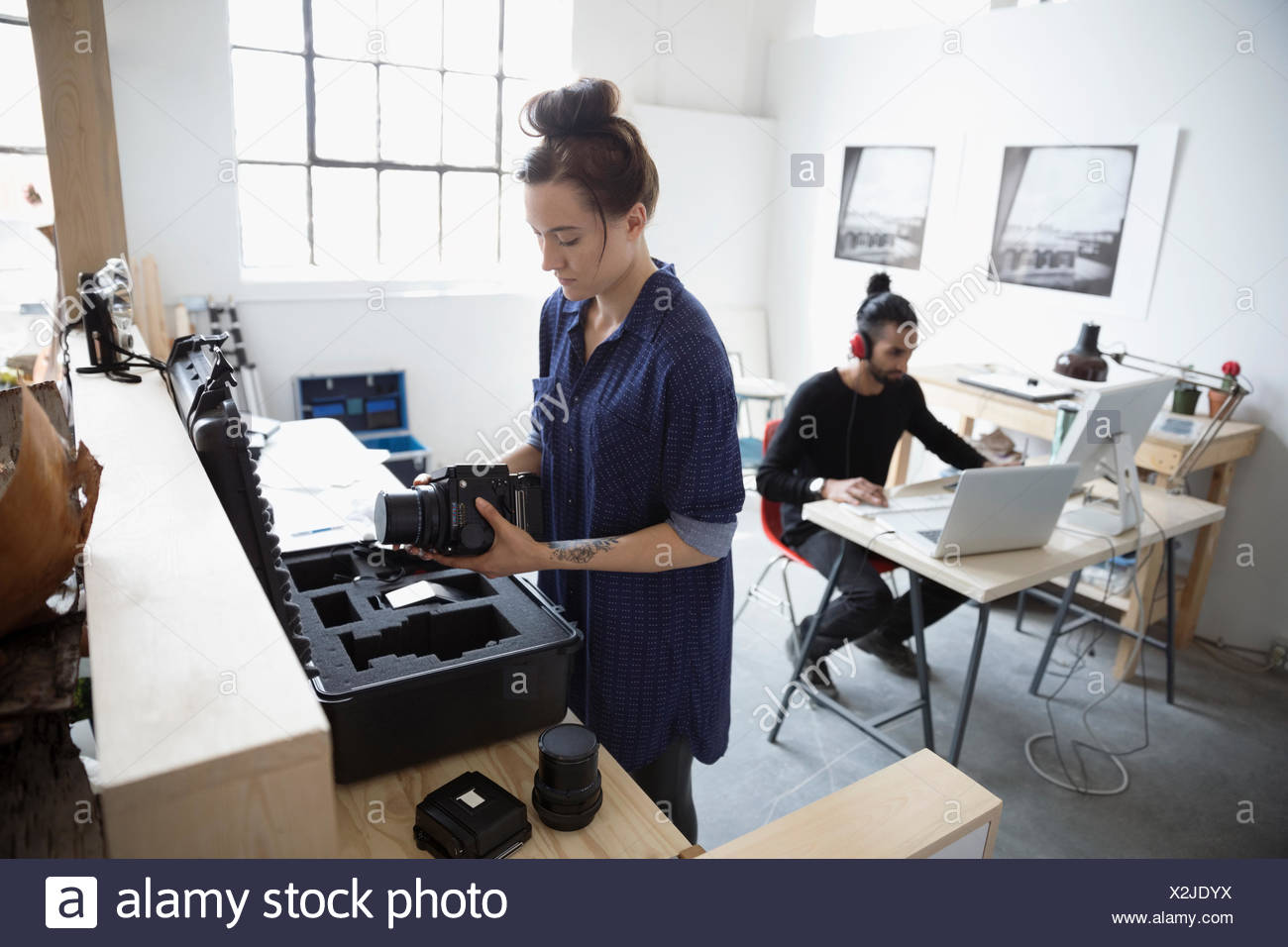 Photographers working at laptop and with camera lenses in art studio - Stock Image