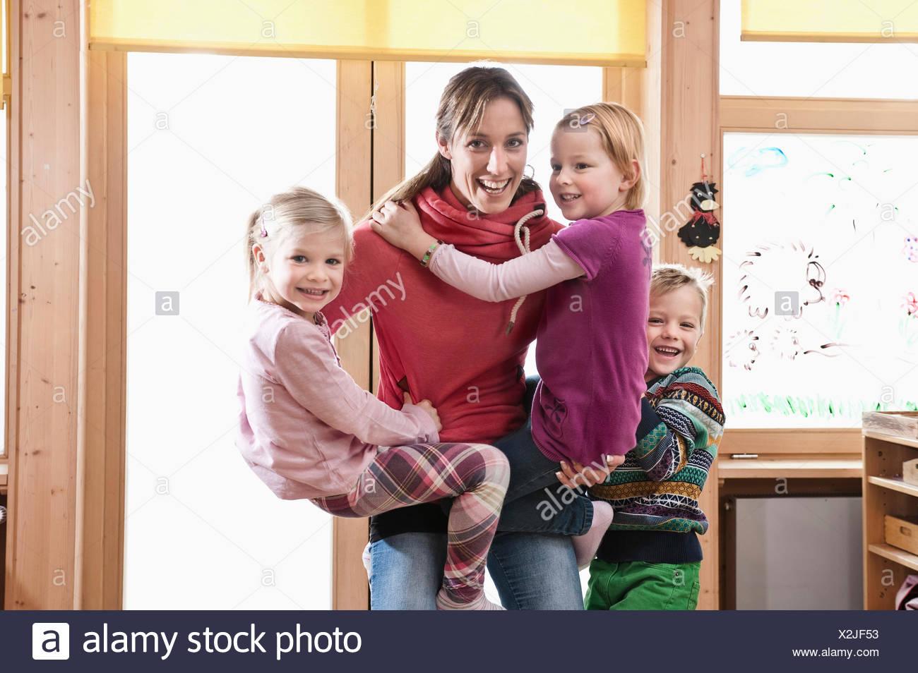 Female educator rampaging with three kids in kindergarten - Stock Image