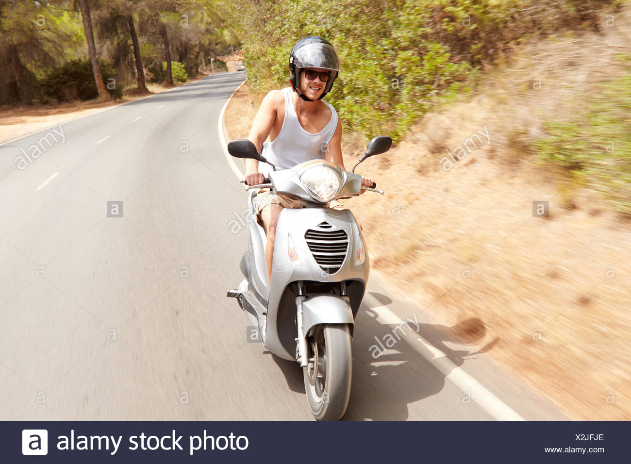 Young Man Riding Motor Scooter Along Country Road - Stock Image