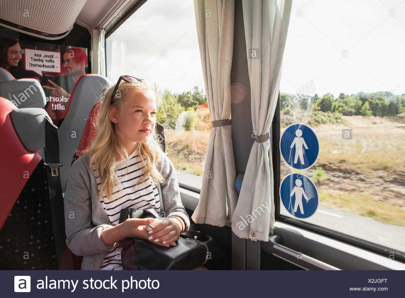 Teenage girl sitting on train - Stock Image