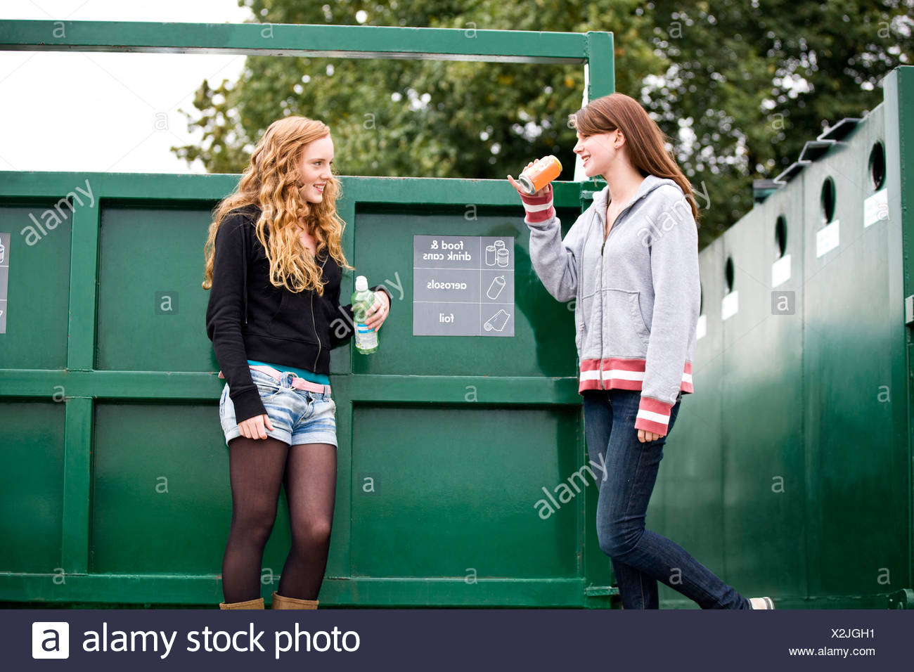 Two teenage girls standing next to a recycling container, drinking soft drinks - Stock Image