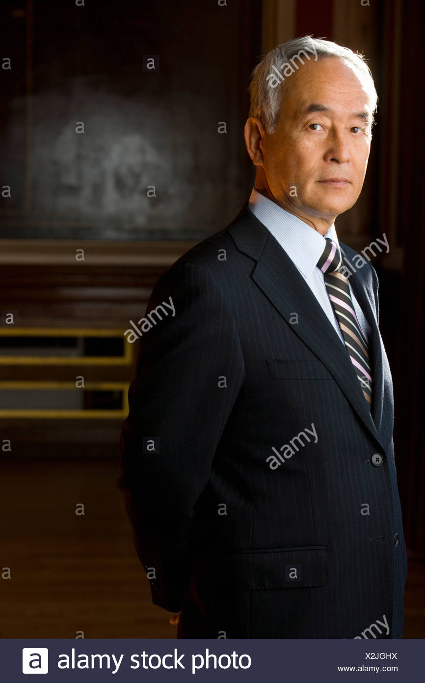 Portrait of businessman with arms behind back - Stock Image