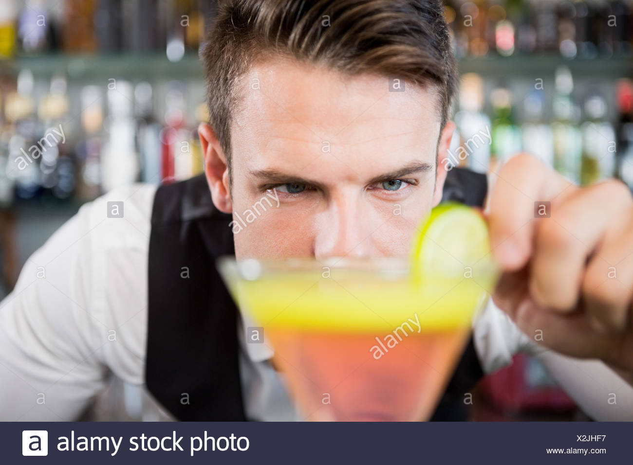 Waiter decorating cocktail with lime - Stock Image