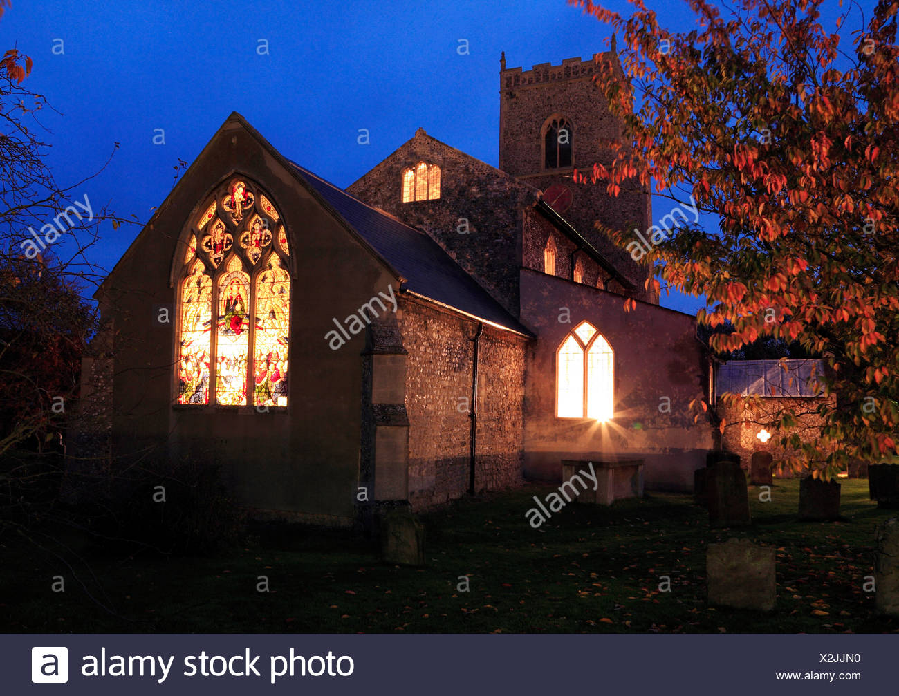 Brancaster Church, east window lights glowing through stained glass window at night, Norfolk, England UK - Stock Image