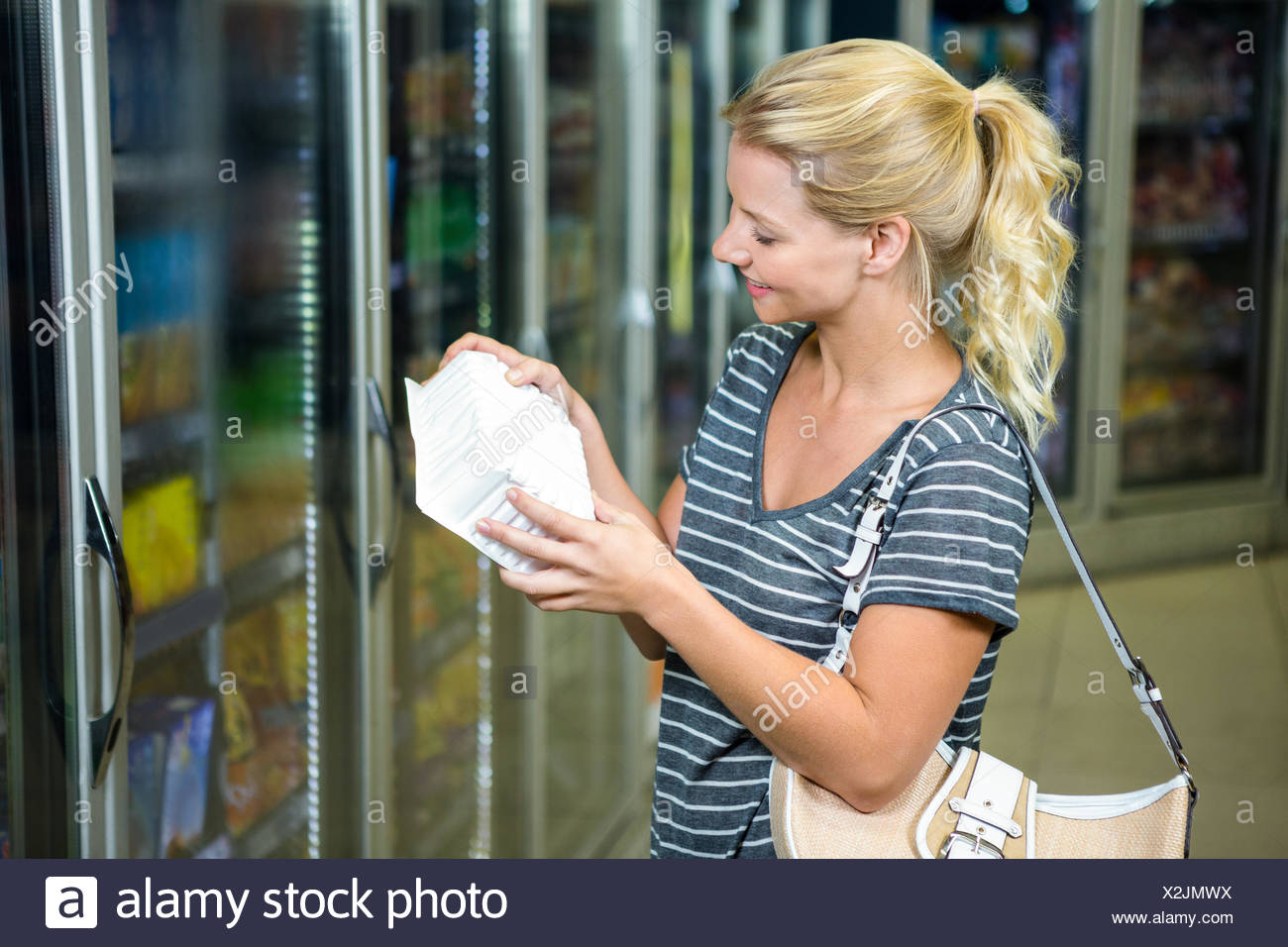 Blonde woman looking at product Stock Photo
