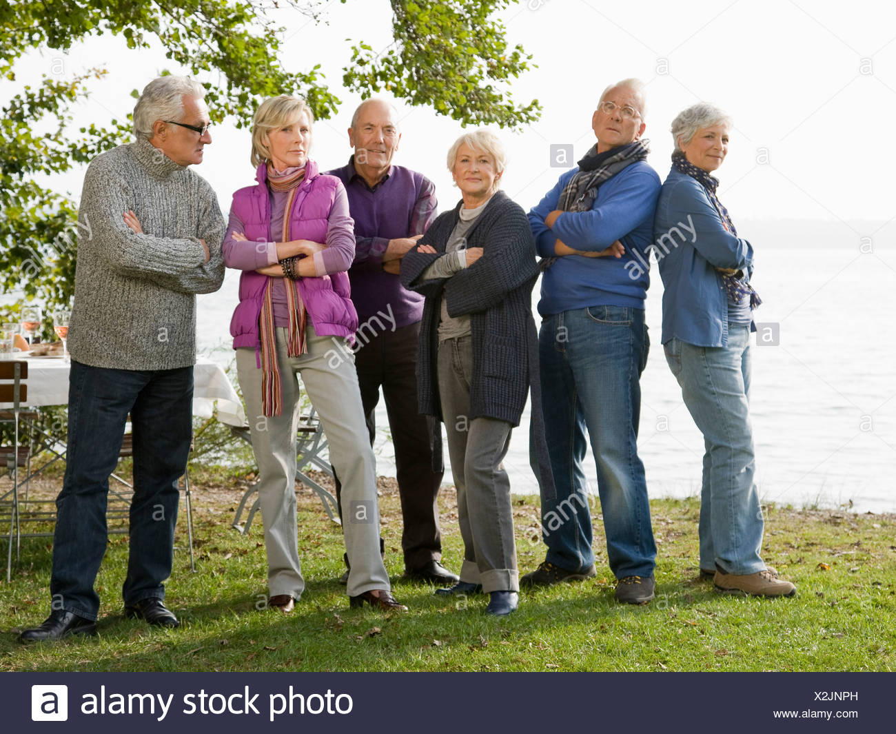 Six senior friends standing next to a lake with arms folded - Stock Image
