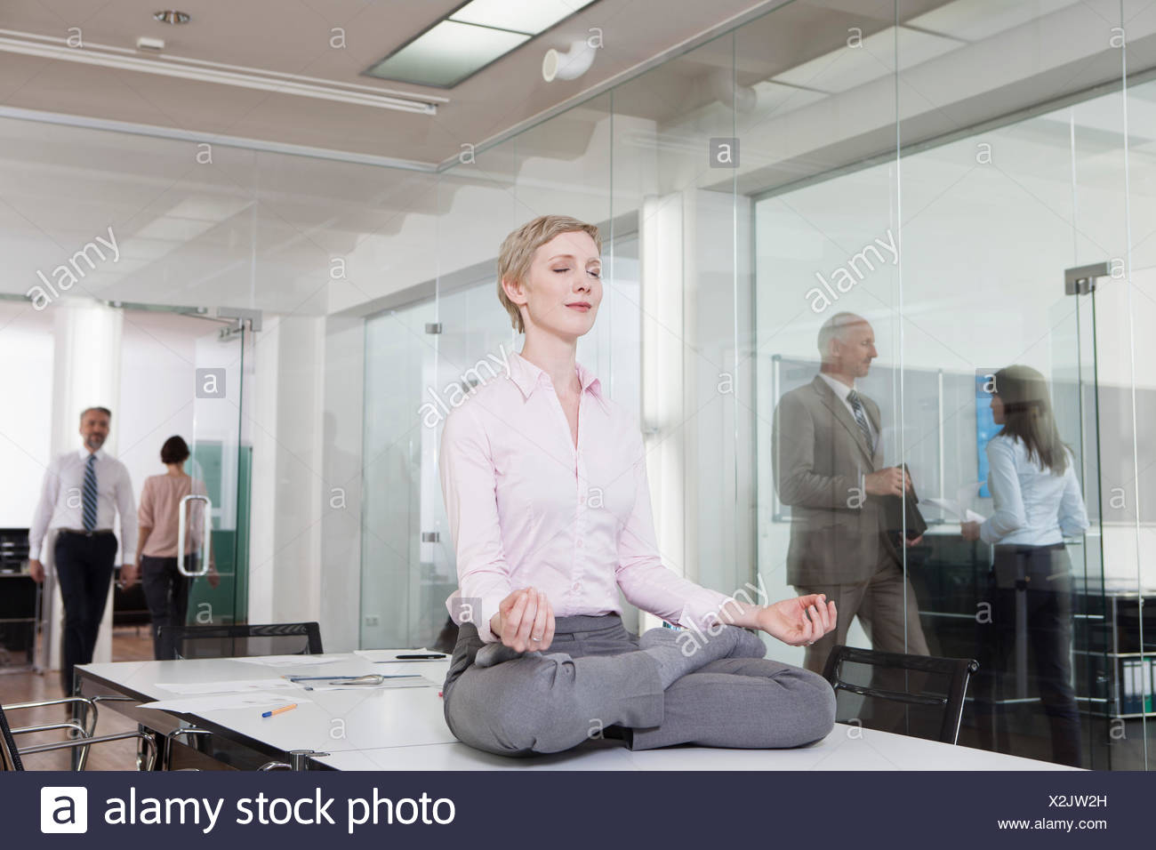 office meditation. Germany, Munich, Businesswoman In Office, Meditating On Desk - Stock Image Office Meditation