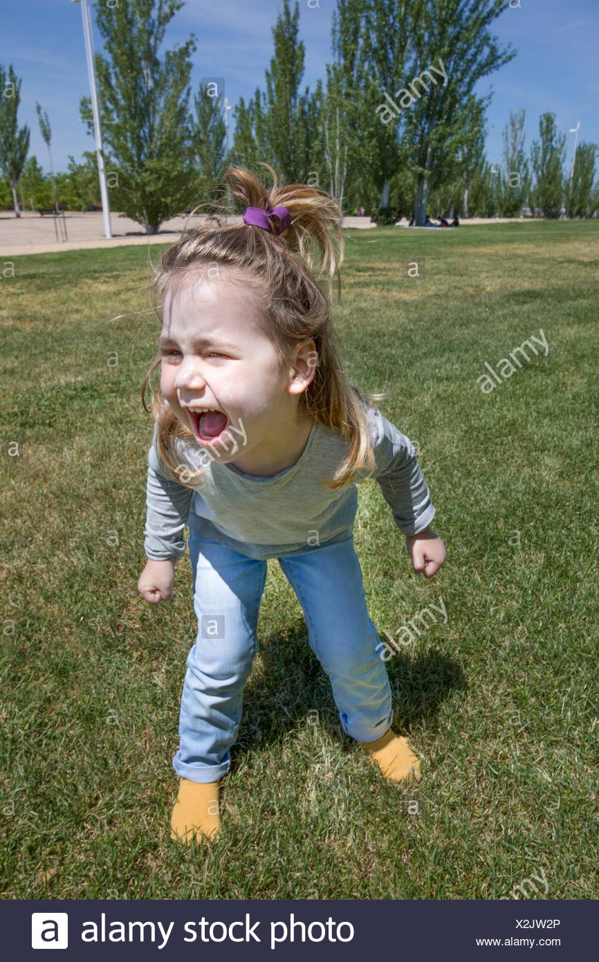 three years old blonde child, with pigtail and blue jeans, standing and shouting in green grass in public park named Juan Carlos, in Madrid, Spain, - Stock Image