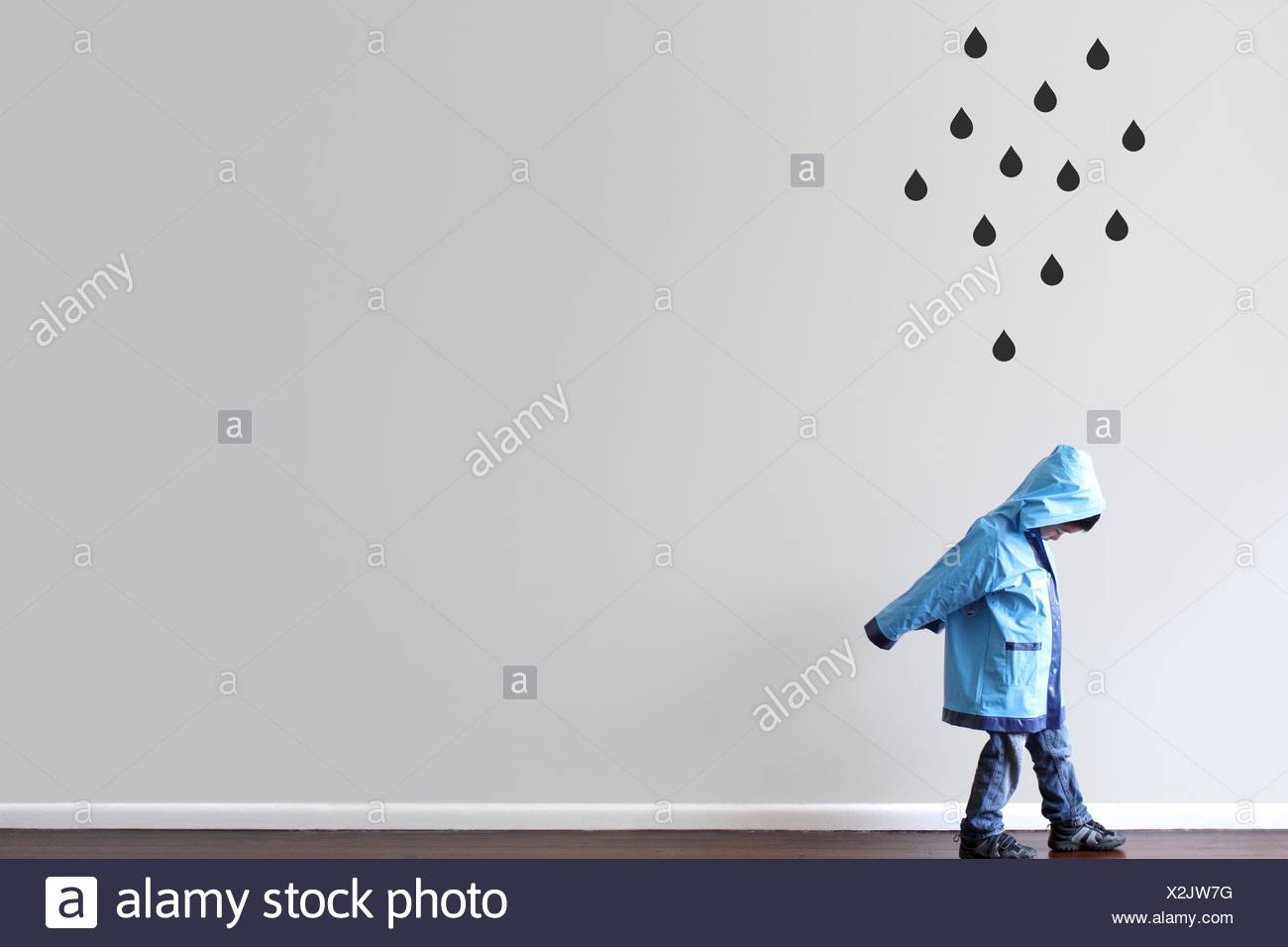 Boy in raincoat walking past a wall with black raindrops painted on the wall - Stock Image