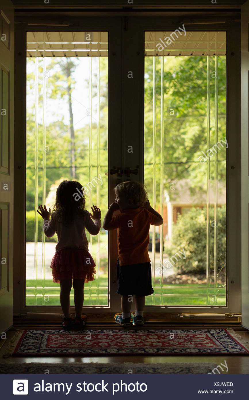 Male and female toddler friends silhouetted by patio door - Stock Image