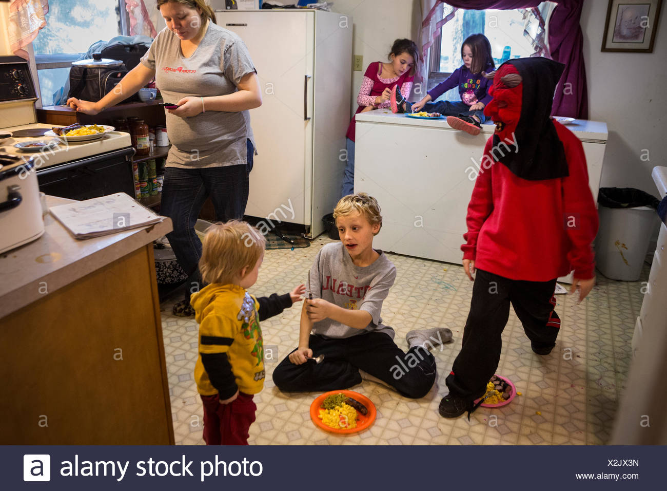 Dinner is a haphazard affair for a financially struggling family. - Stock Image