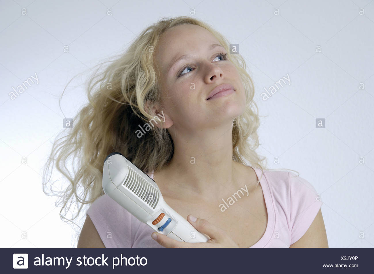 hair dry hairdrier hairdryer young woman young blond portrait studio inside - Stock Image