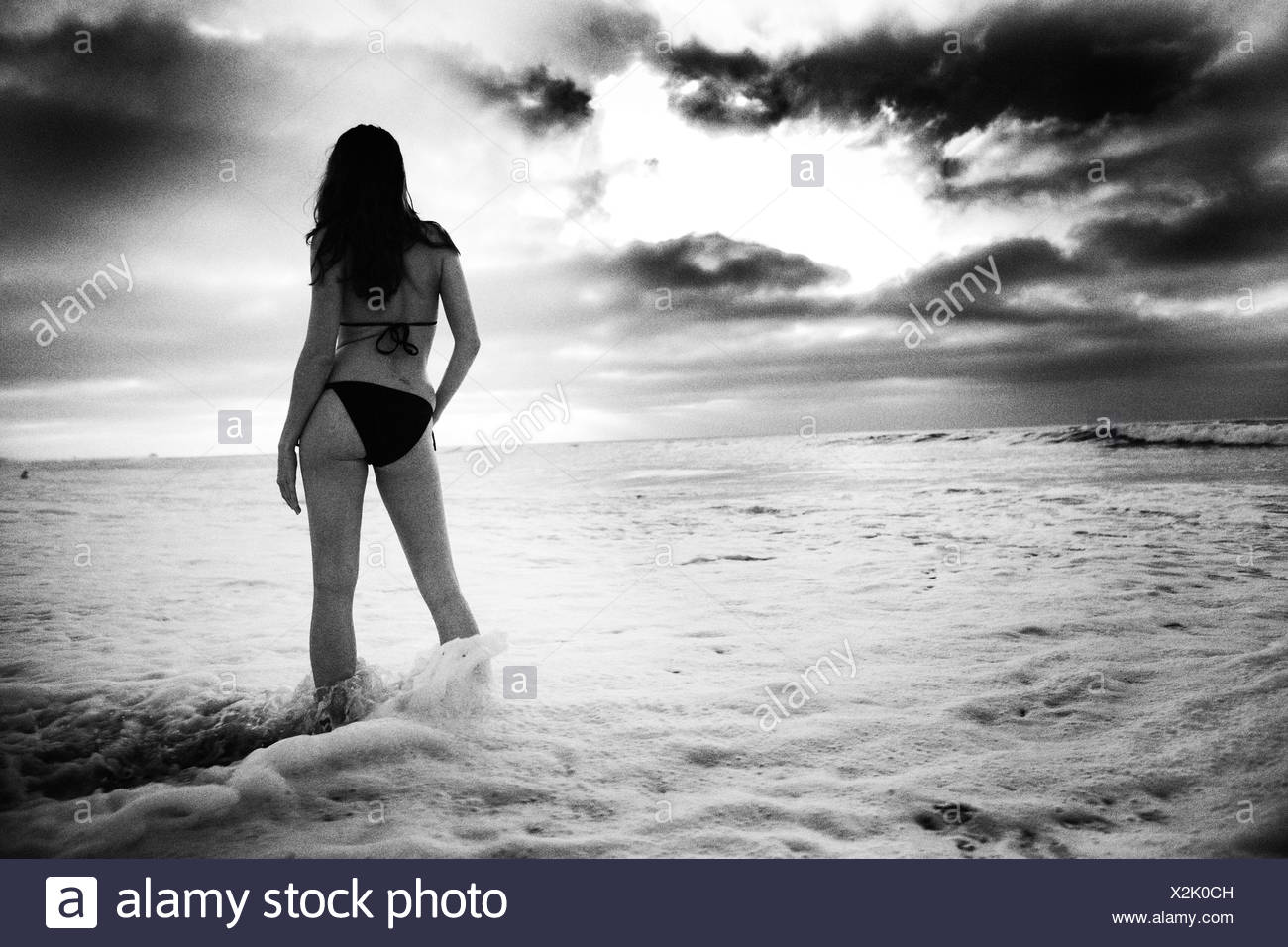 A bikini girl looks out to the sunset. - Stock Image