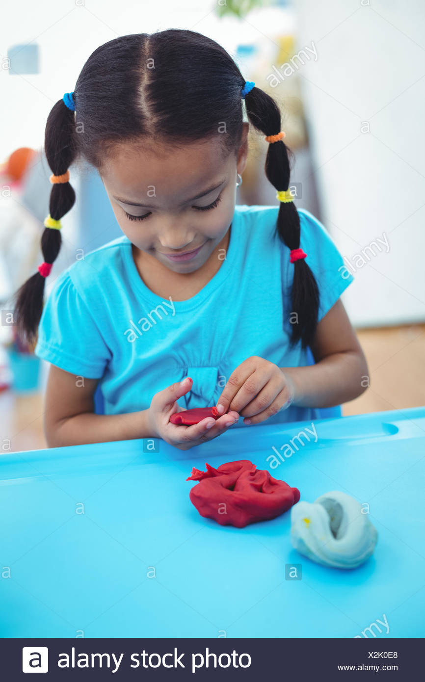 Smiling girl using modelling clay - Stock Image