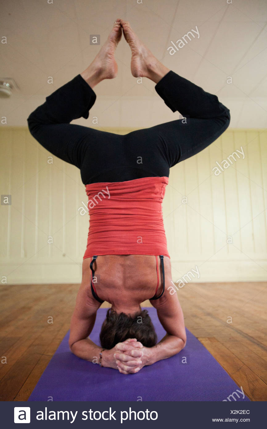 An older woman performs a more advanced technique of yoga in a small studio. Stock Photo
