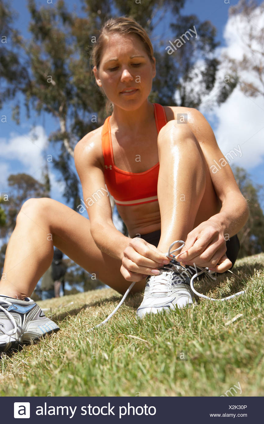 Woman tying trainer shoelace in park sitting on grass close up surface level tilt - Stock Image