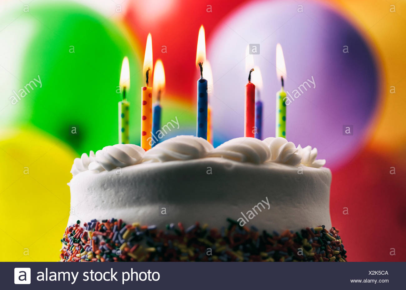 Lighted Birthday Candles On A Cake In Front Of Balloons