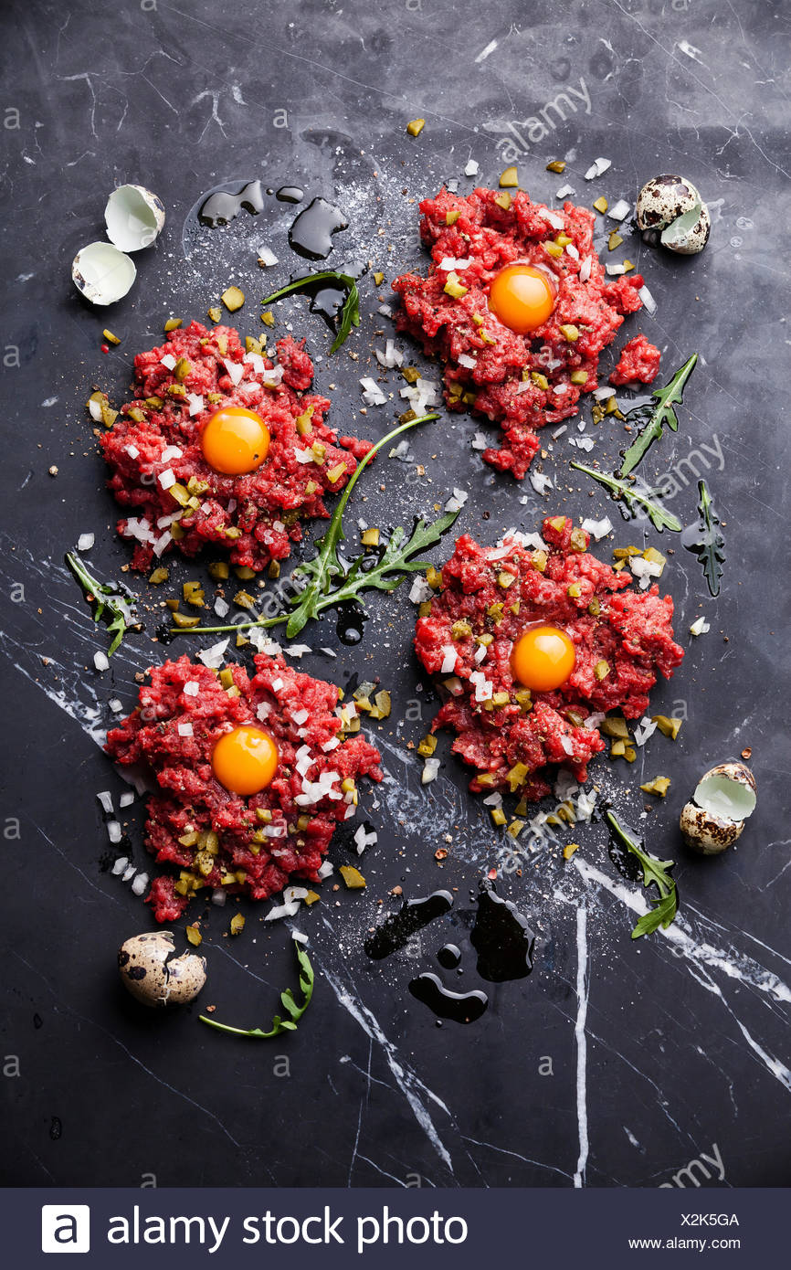 Beef tartare with pickled cucumber and fresh onion on dark marble background Stock Photo