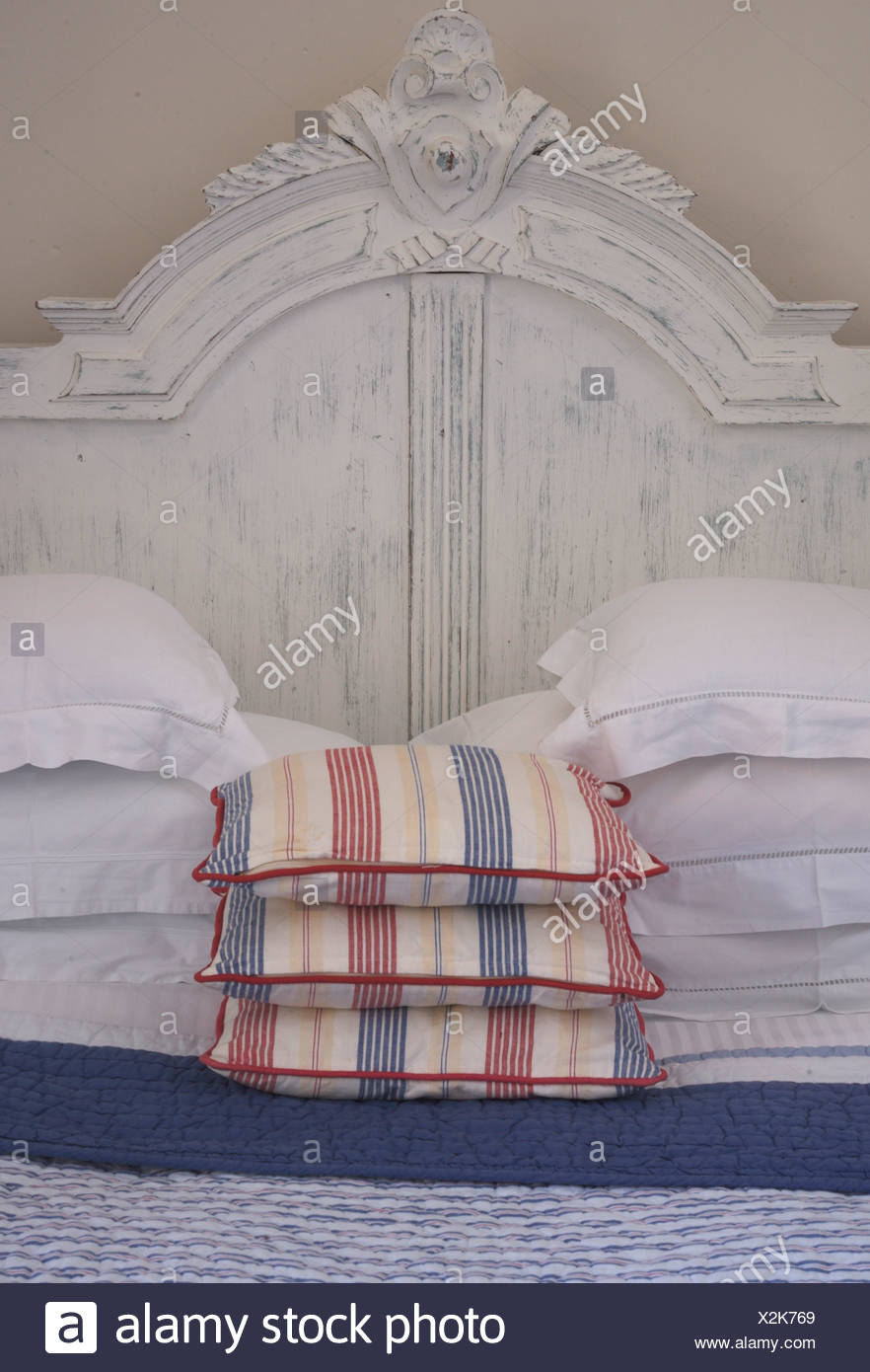 White Pillows And Striped Cushions On Double Bed With Painted White Wood Headboard Stock Photo Alamy