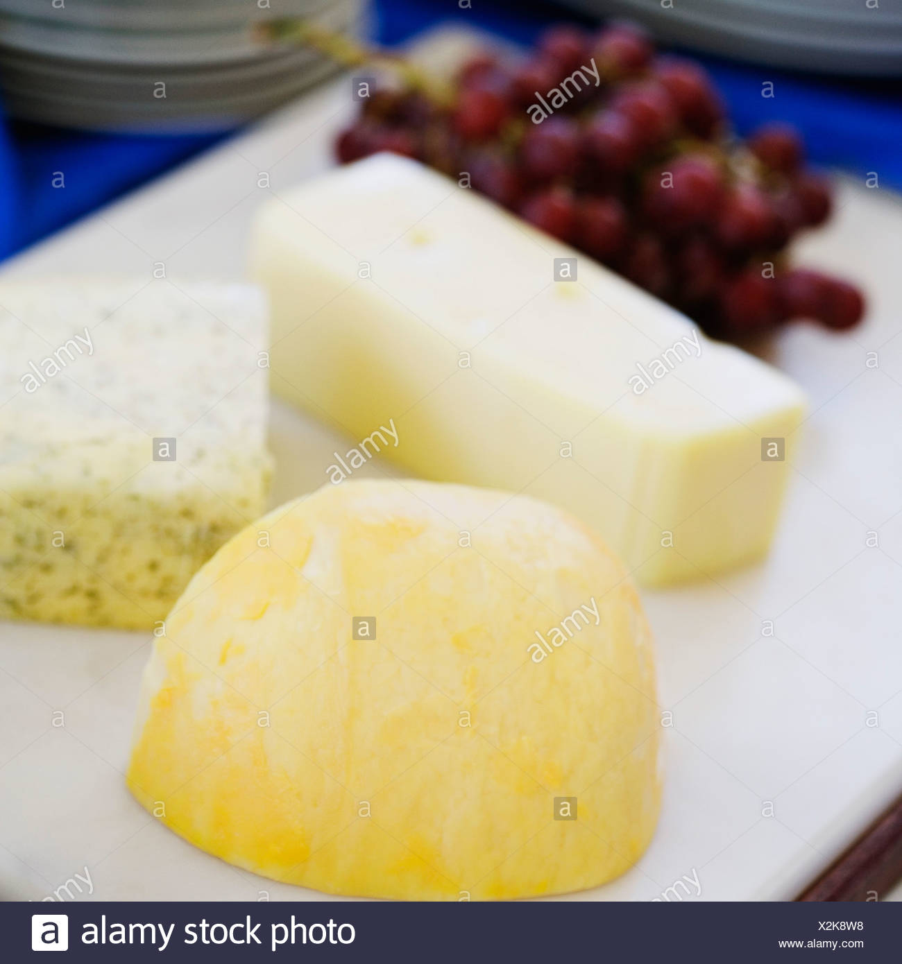 Close-up of slices of cheese with red grapes on a cutting board - Stock Image