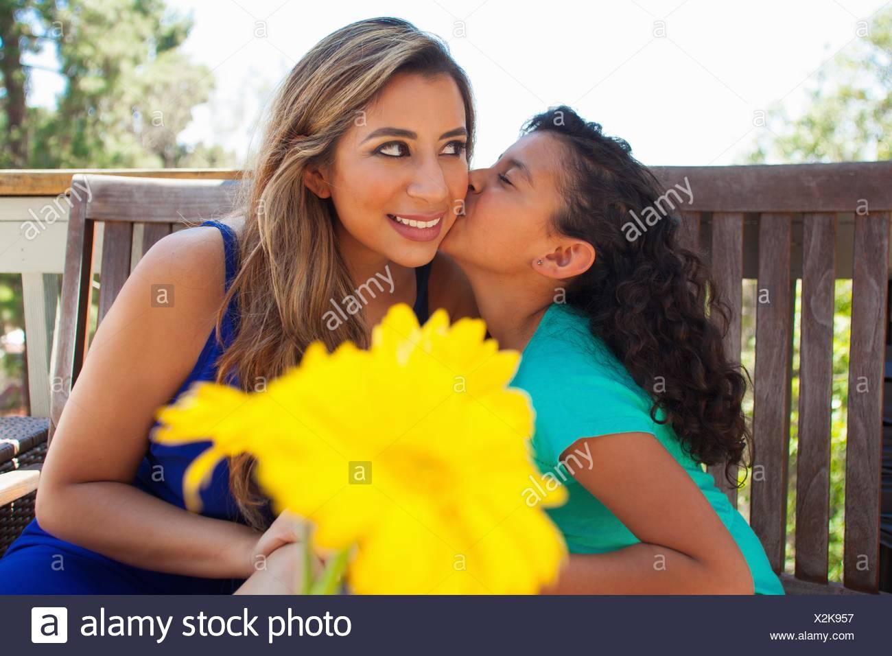 Girl kissing her mothers cheek on garden bench - Stock Image