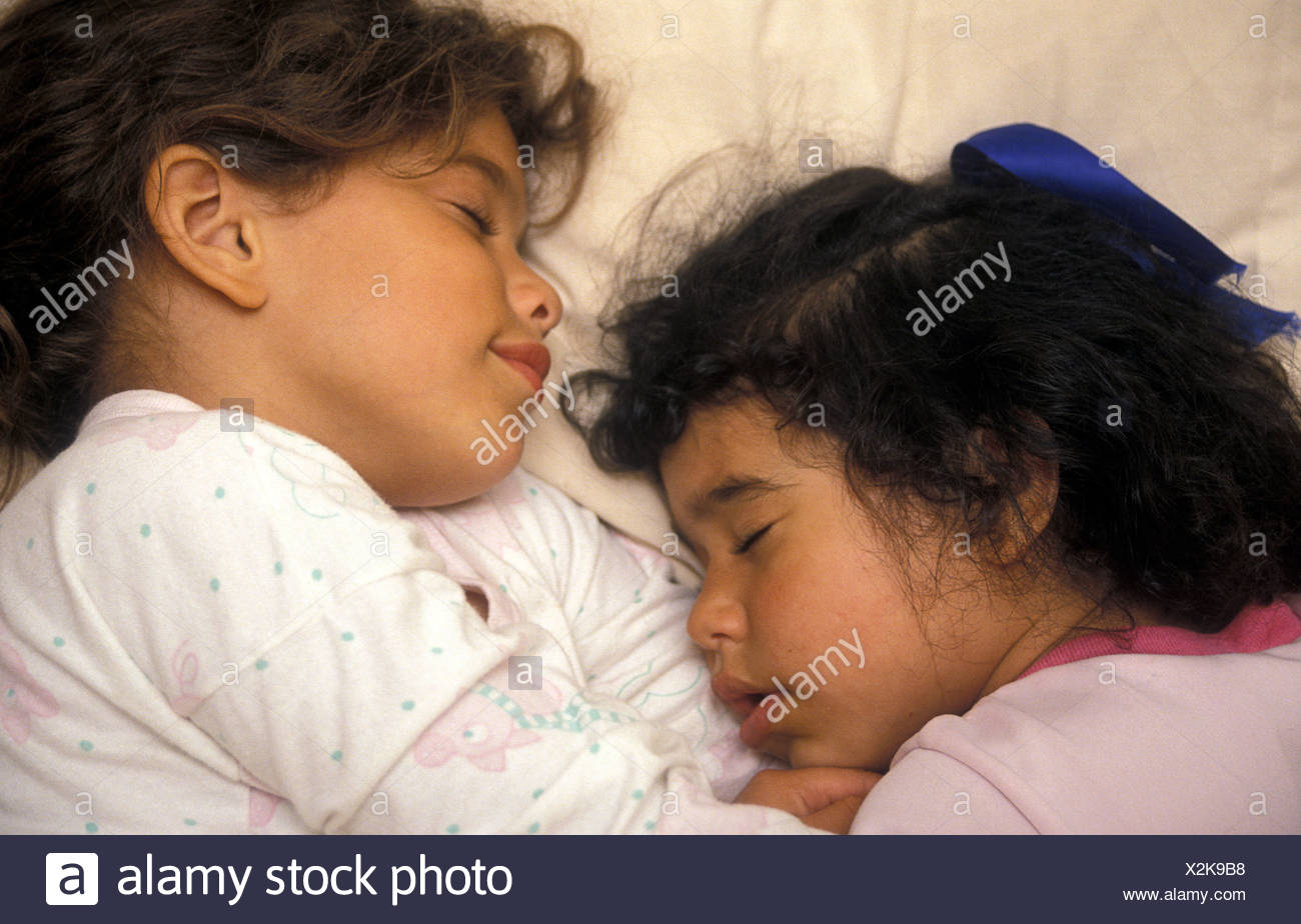 two little sisters alseep in bed - Stock Image