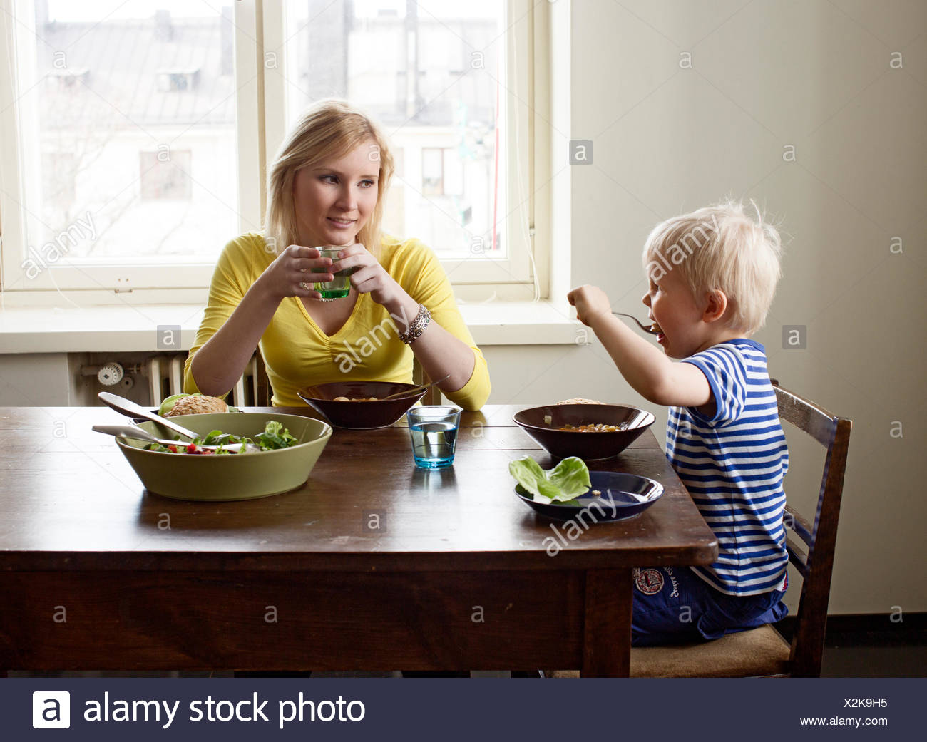 Finland, Helsinki, Kallio, Mother and son having lunch - Stock Image