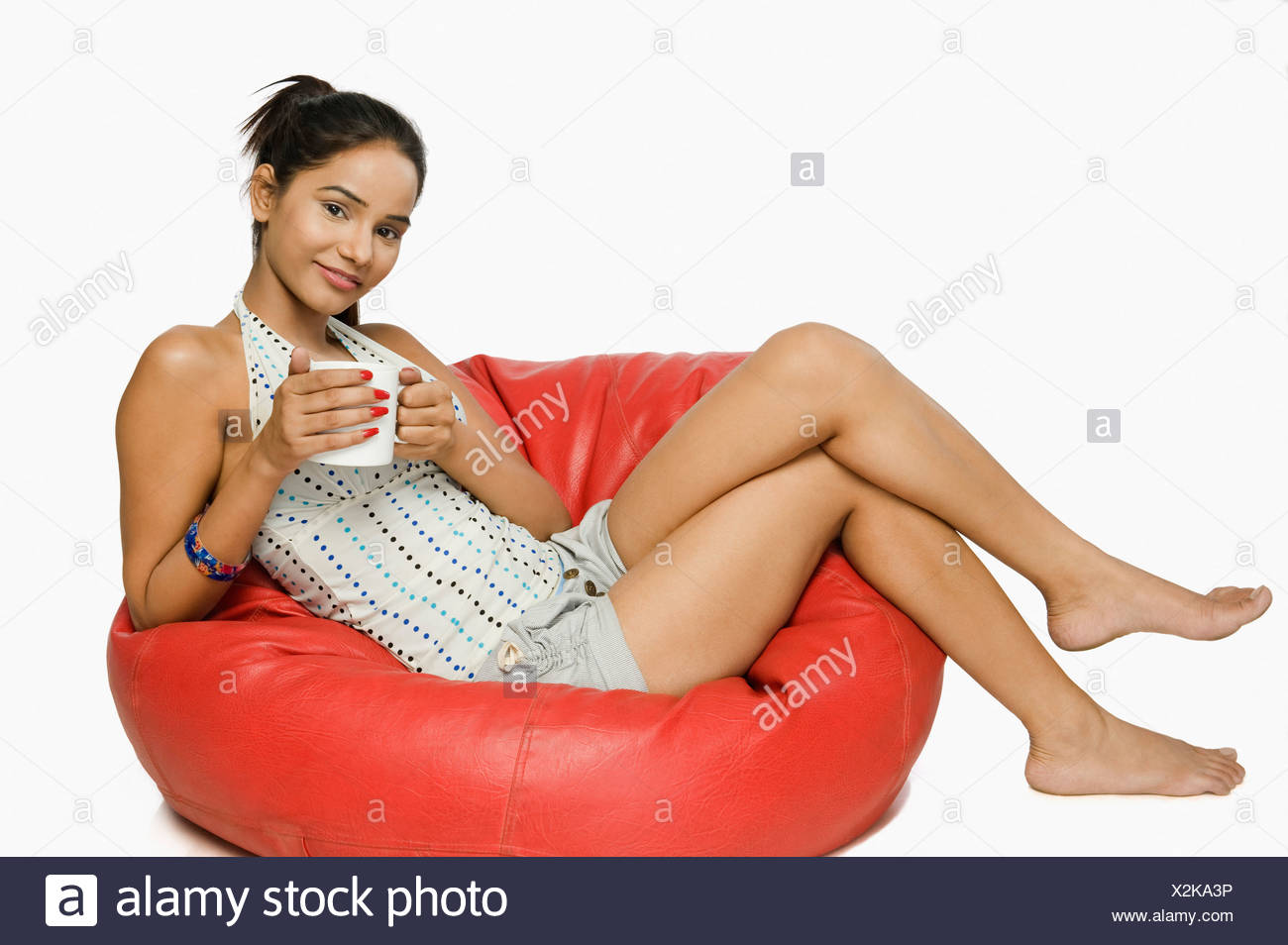Woman sitting on a bean bag with a cup of coffee - Stock Image