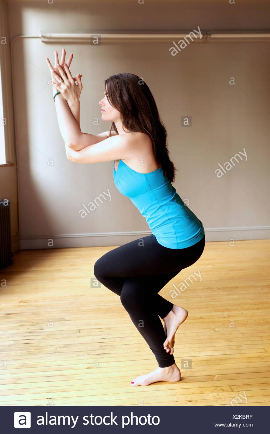 Young woman doing eagle pose - Stock Image