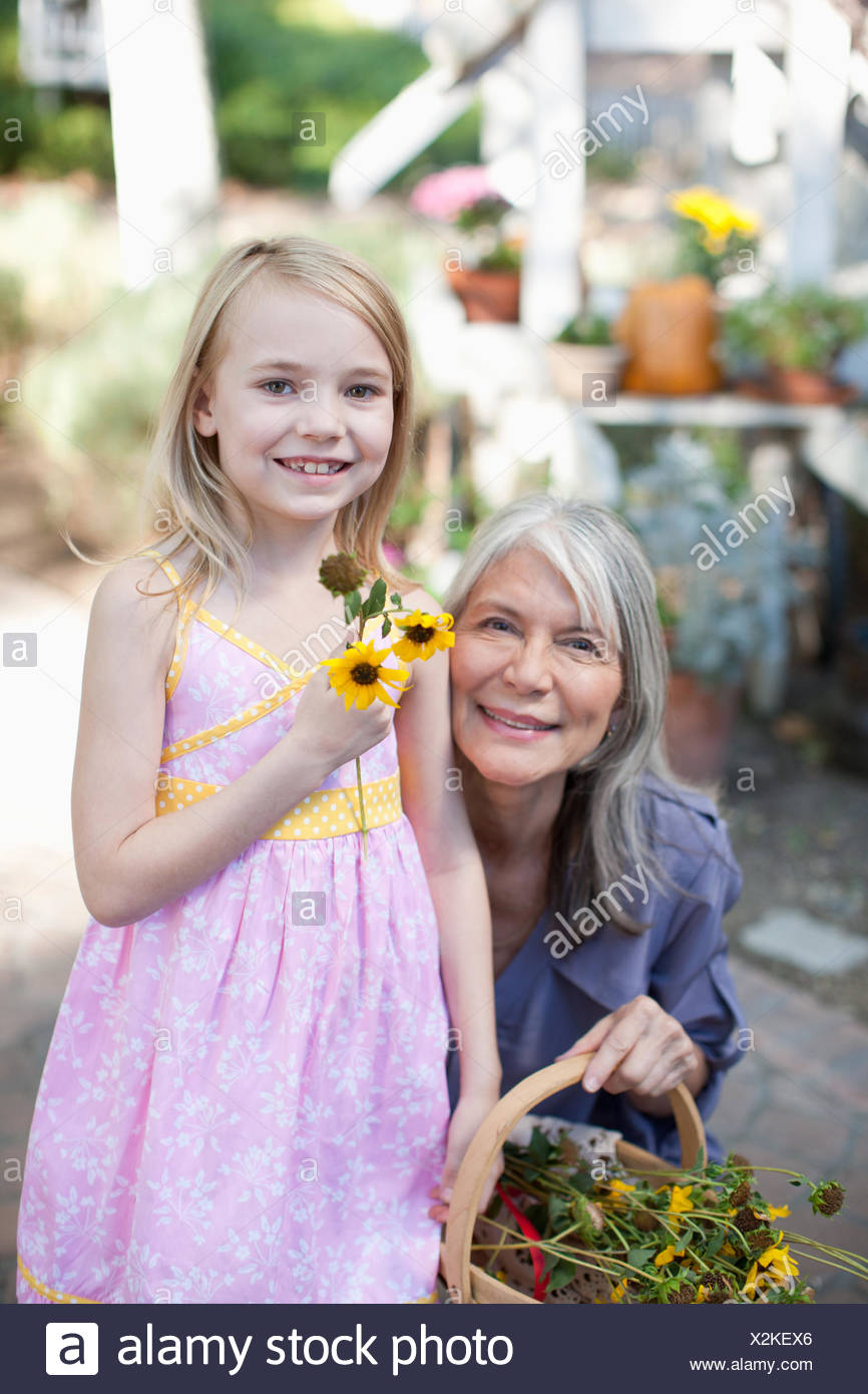 Older woman and granddaughter picking flowers - Stock Image