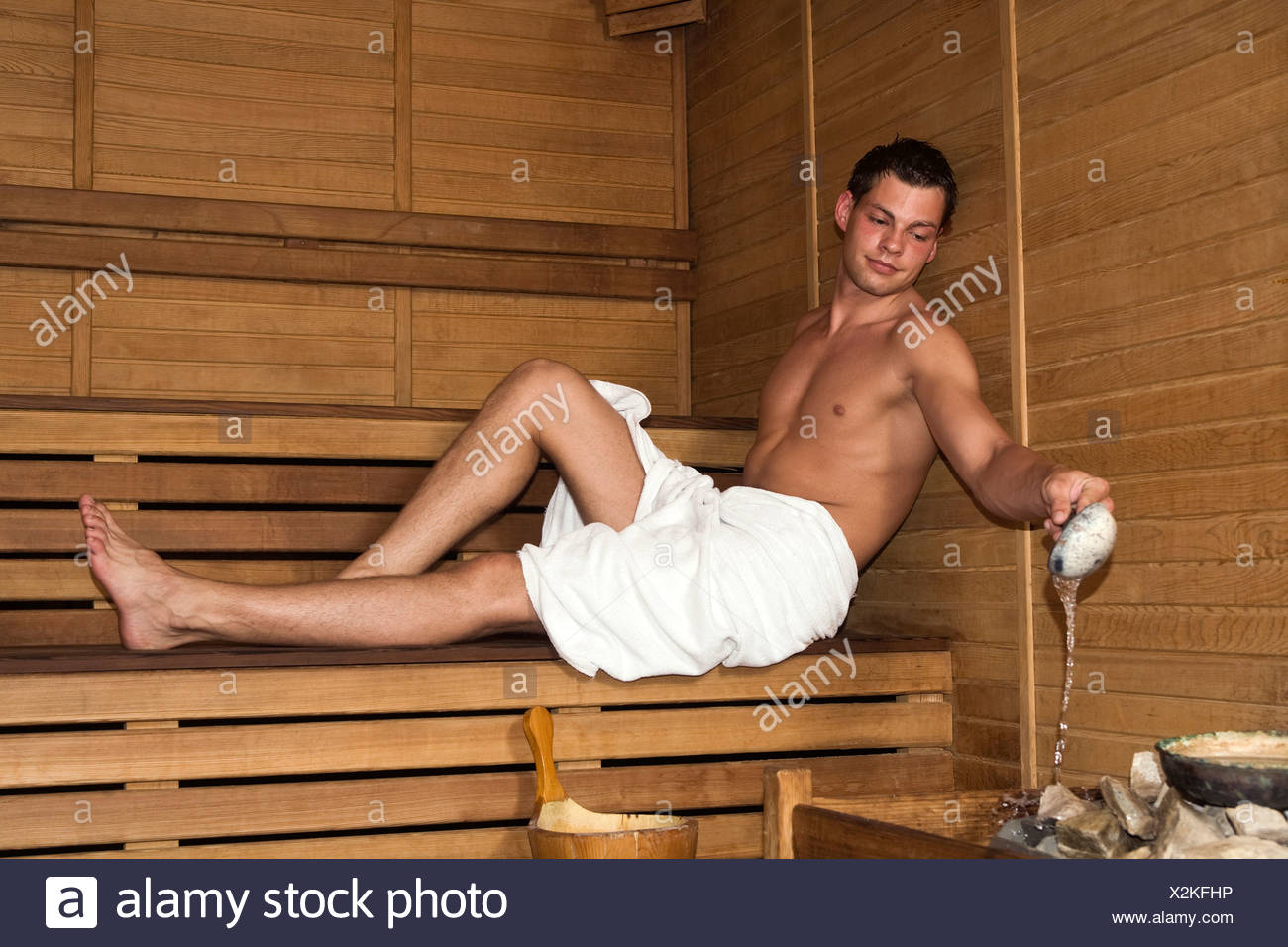 Turkey, Young man in sauna pouring water on stones - Stock Image