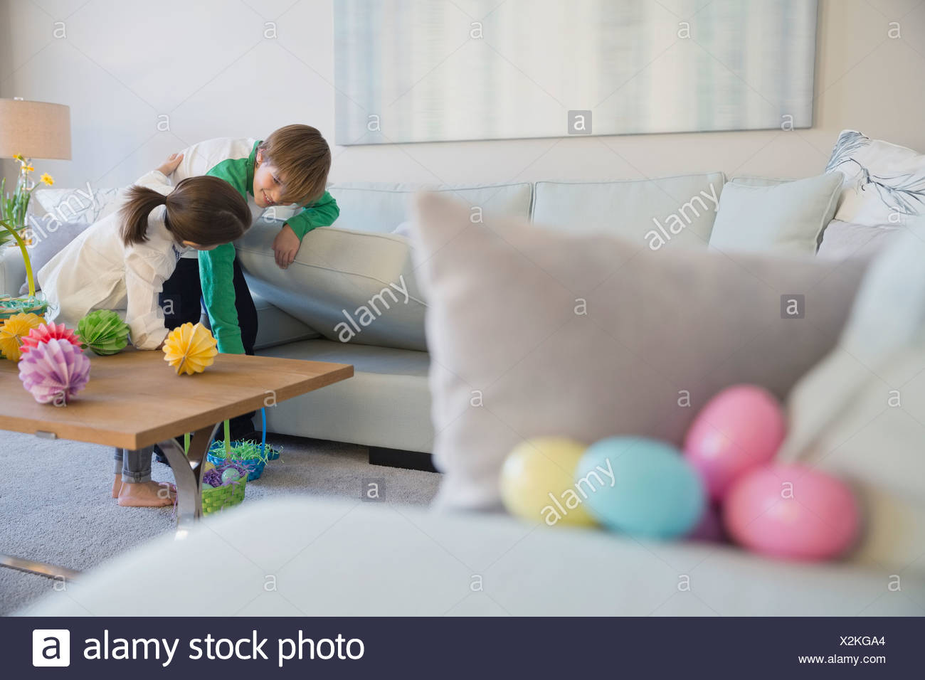 Siblings searching for Easter eggs in living room - Stock Image