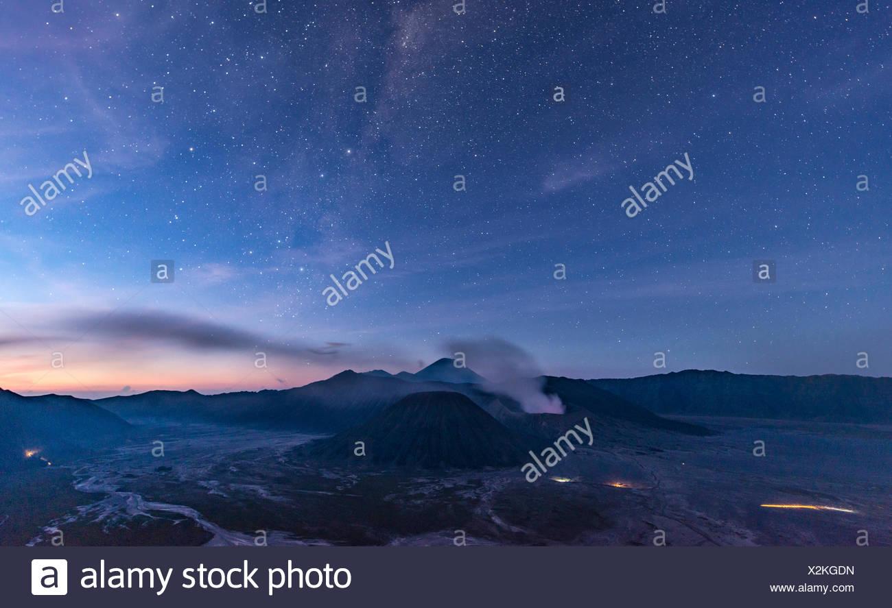 Night sky with stars, smoking volcano Mount Gunung Bromo, Mount Batok in front, Mount Kursi at back, Mount Gunung Semeru, Bromo - Stock Image