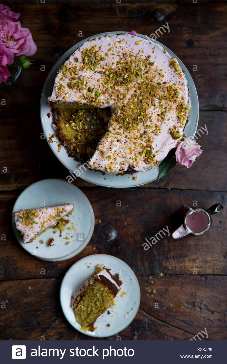 Pistachio and Rose Cake, Sliced to Serve with Jug of Icing - Stock Image
