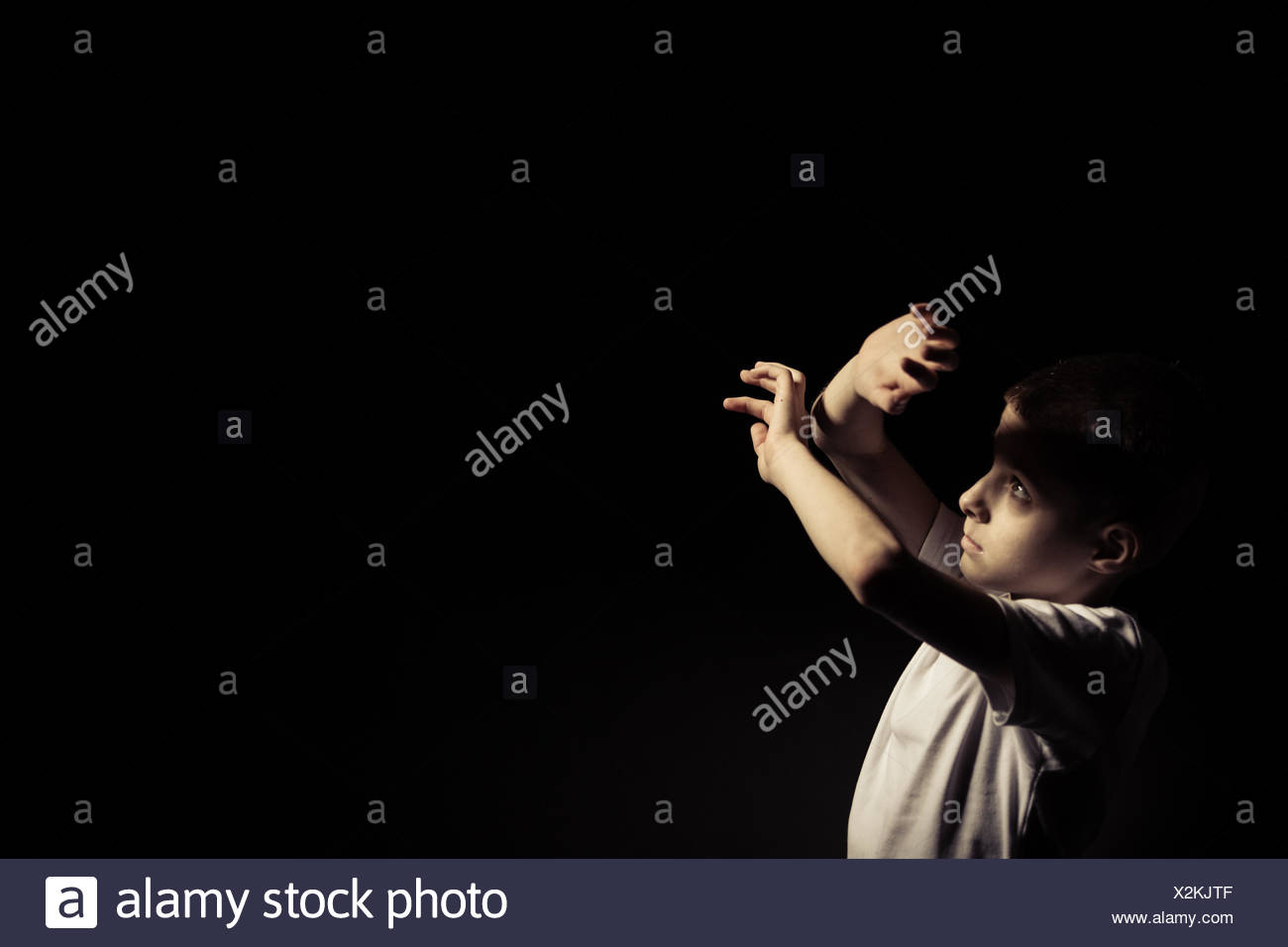 Boy Looking Up While Covering Light Against Black - Stock Image