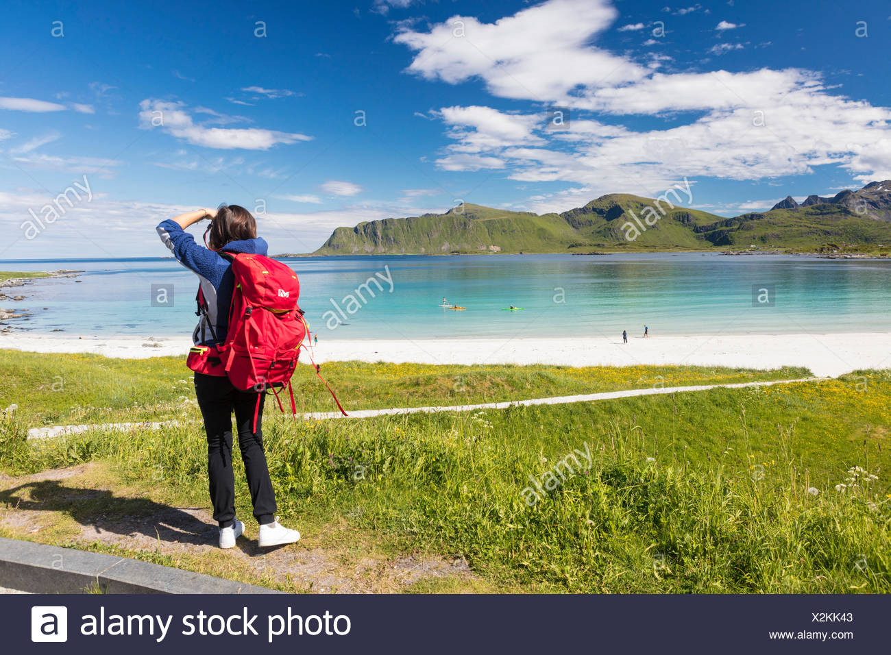 Photographer in action in the green meadows surrounded by turquoise sea and fine sand Ramberg Lofoten Islands Norway Europe - Stock Image