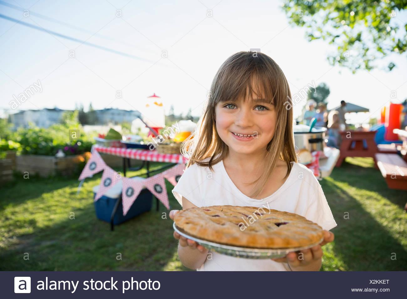 Portrait smiling girl holding fresh baked pie park - Stock Image