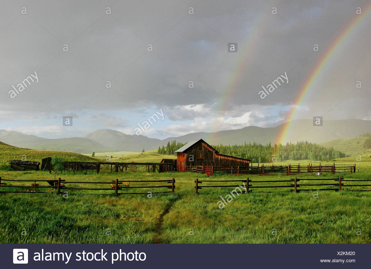 Old barn and rainbow after rainstorm, Creed, Colorado, USA - Stock Image