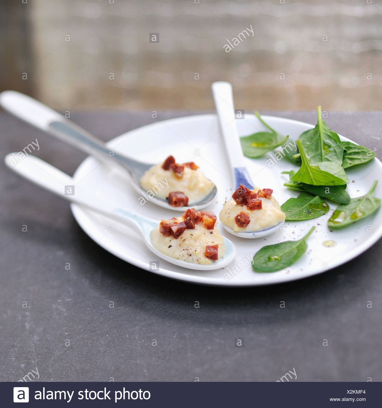 Spoonfuls of scrambled eggs with diced chorizo - Stock Image