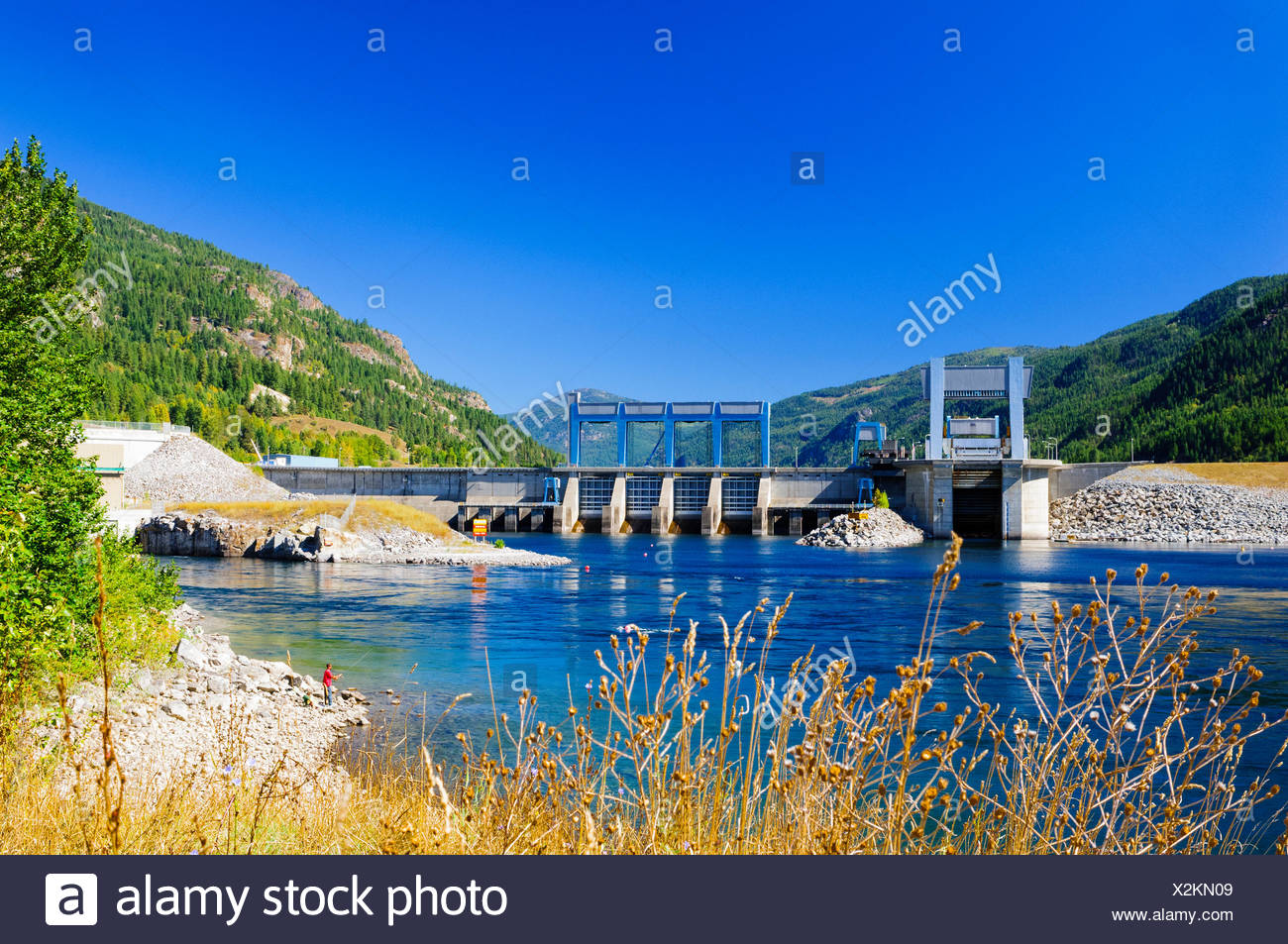A man fishing near the Hugh Keenleyside Dam on the Columbia River near Castlegar, British Columbia. - Stock Image