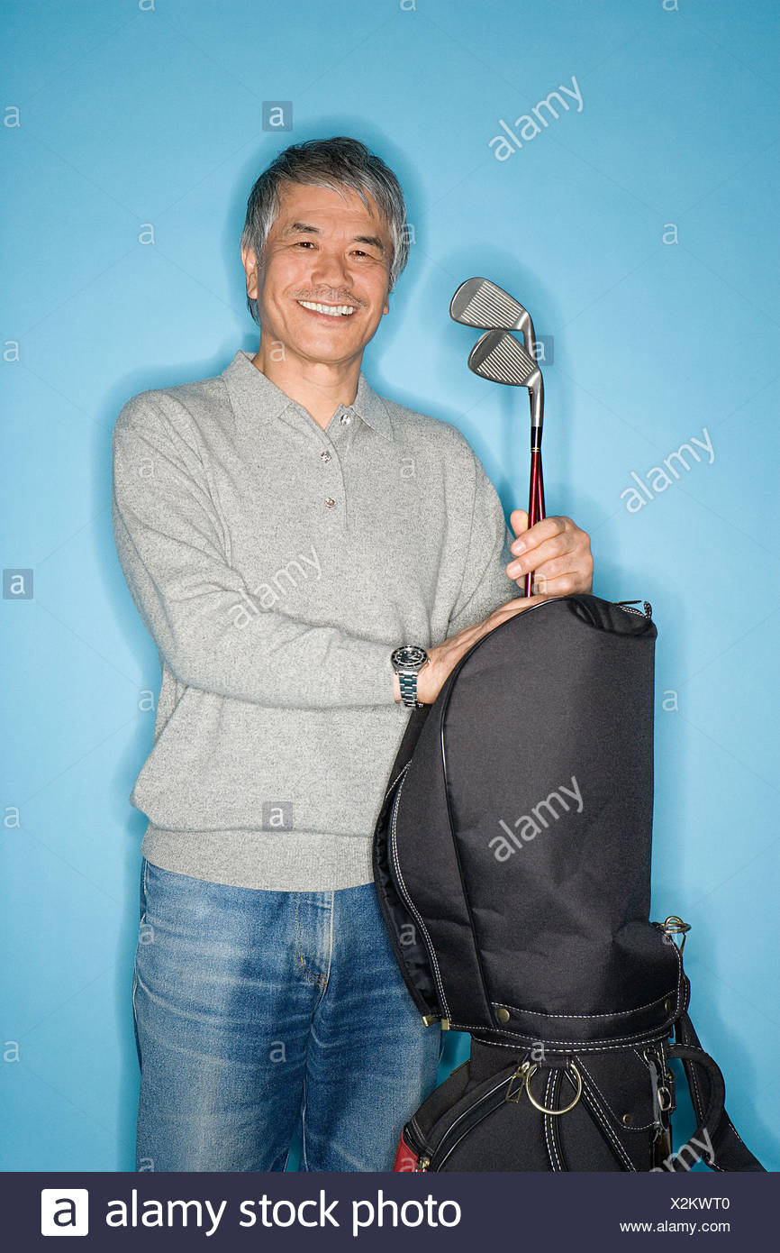 Man with golf clubs - Stock Image