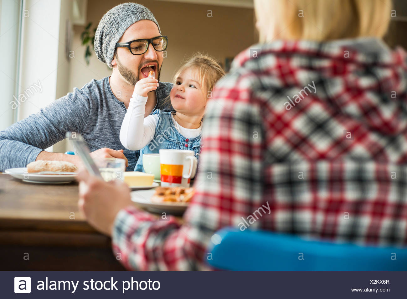 Daughter feeding father at dining table - Stock Image