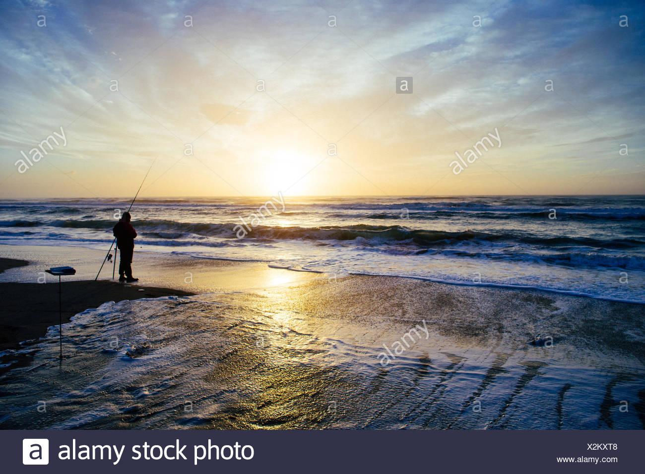 Silhouette of a Fisherman on the beach at sunset, Pescia Romana, Lazio, Italy - Stock Image