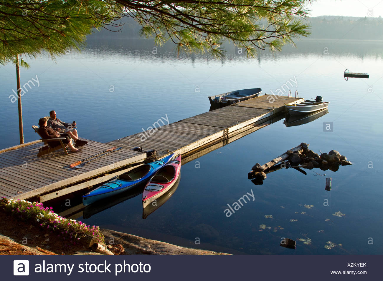 Middle-aged couple enjoy quiet morning on dock near their cottage, Source Lake, Algonquin Park, Ontario, Canada. - Stock Image