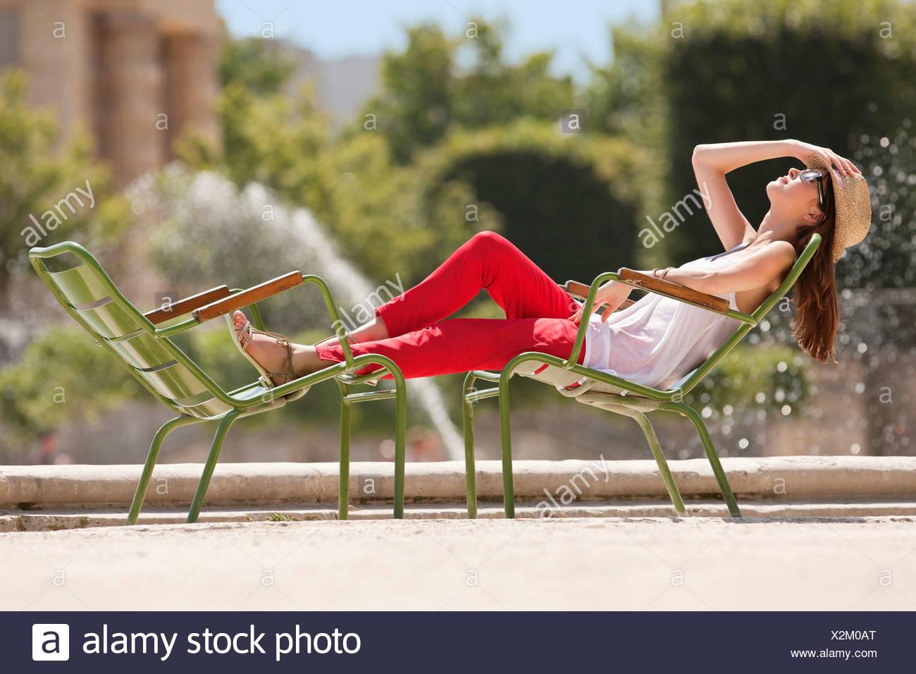 Woman resting in a chair near a pond, Bassin octogonal, Jardin des Tuileries, Paris, Ile-de-France, France - Stock Image