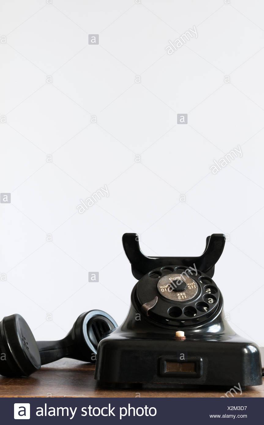 Altes Telefon auf einem Schreibtisch und weissem Hintergrund fuer Textfreiraum. - Stock Image