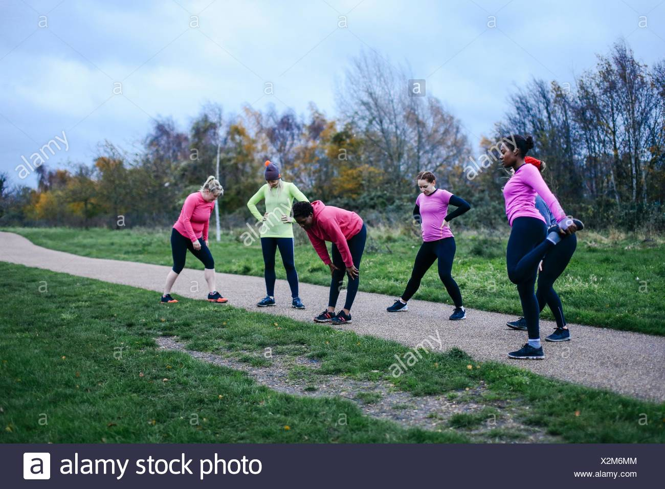 Six adult female runners warming up together on park path Stock Photo